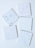 Five different stone samples mainly white based with marble like grains and veins. Samples of different stones in square shape stacked on top of each other in Royalty Free Stock Photo