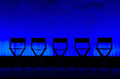 Five Director's Chairs silhouette on Blue Stage. Silhouette of a five traditional wood and canvas Director's Chair on a blue stage background royalty free stock photography