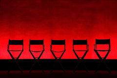 Five Director's Chairs silhouette on Red Stage. Silhouette of a five traditional wood and canvas Director's Chairs on a red stage background - horizontal stock photography