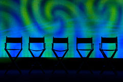 Five Director's Chairs silhouette on Swirl Stage. Silhouette of a five traditional wood and canvas Director's Chair on a blue and green swirl stage background stock image