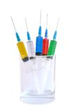 Five disposable syringes in a glass. Against white background Stock Photography