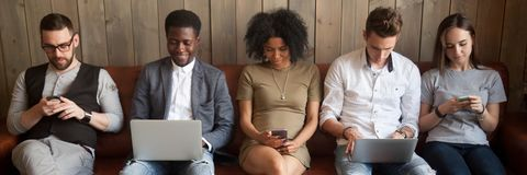 Five diverse businesspeople girls guys sitting on couch using gadgets. Multi-ethnic businesspeople sitting in row on couch absorbed in mobile phones computers stock images
