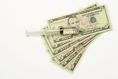Five dollar bills and syringe Stock Images