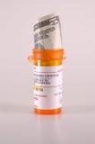 Five dollar medicine. Five dollar bill sticking out of prescription medicine bottle symbolizing cheap medicine Stock Photo