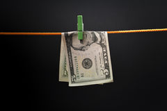Five dollars was fixed on a rope with a green clothespin. Drying, dark background Royalty Free Stock Photos