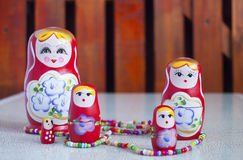 Five dolls and colored beads on the table Stock Photography