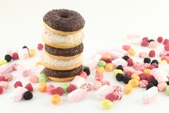 Five donuts, many bright candies and marshmallows Stock Image