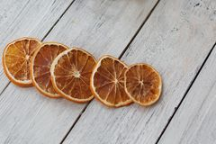Five dried fragrant oranges slices on a white wooden background closeup royalty free stock photo