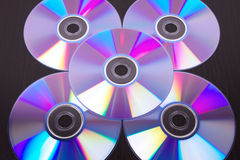 Five dvd discs on black wooden table Stock Photo