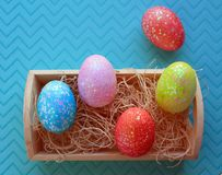Five colorful Easter eggs in nesting box on purple background. Five Easter eggs on blue pink yellow and red in a nesting box. With nesting material above shot royalty free stock images