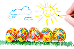 Five easter eggs on grass, sun in sky Royalty Free Stock Image