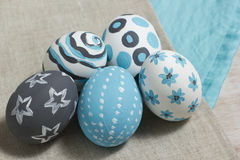 Five Easter eggs on gray cotton fabric. To paint boiled eggs on Easter tradition of Christians Stock Image