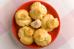 Five eclaires on a red plate. Five cream puffs on a red plate. Close up shoot stock photography