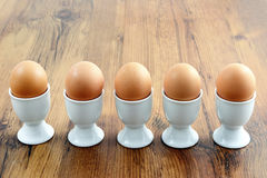 Five egg cups with natural brown eggs in a row on table Stock Images