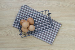 Five eggs in iron basket. Antique iron basket with chicken eggs on tablecloth on top of a wooden table Stock Photos