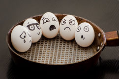 Five eggs with painted emotions in a frying pan, a food concept.  Stock Photo