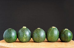 Five Eight Ball Squashes. Five raw eight ball squashes in a row on a natural wooden board against a black textured wooden background Royalty Free Stock Photo