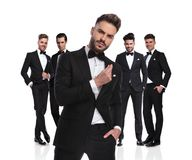 Five elegant groomsmen standing with arrogant leader in front. Five elegant groomsmen standing on white background, dressed in black tuxedoes,with arrogant royalty free stock photo