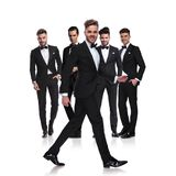 Five elegant men in tuxedoes with leader walking to side royalty free stock images