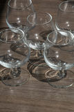Five empty cognac glasses on the brown wood. With shadows Royalty Free Stock Photos