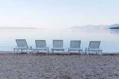 Five empty deck chair and distant mountains Stock Photos