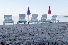 Five empty deck chair and parasol from a low angle Royalty Free Stock Photo