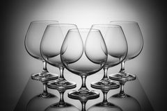 Five empty glasses for brandy with reflections Stock Photo