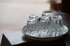 Five empty glasses put upside down on white tray on wood table w Royalty Free Stock Image