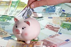 Five Euro. Hand with Euro note and piggy bank on Euro bills royalty free stock photos