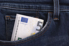 Five euro banknote in a pocket of blue jeans Stock Photos