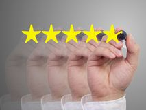 Five fading hands with a pen giving a five star review. On grey background stock photos