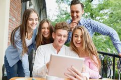 Cheerful friends excited about new tablet at the cafe background. Connection and technology concept. Royalty Free Stock Image