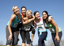Five Female Runners Training For Race. Smiling To Camera Stock Photo