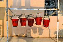 Five fire buckets hanging on a wall in India Royalty Free Stock Photography