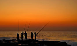 Five fishermen at dawn. Fishermen forming a silhouette against the orange dawn sky Royalty Free Stock Photos