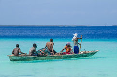 Five fishermen paddling a wooden boat Royalty Free Stock Photo