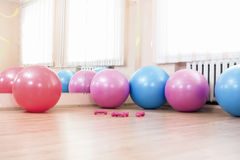 Five Fitballs and Barbells On Floor in Sport Fitness Center Royalty Free Stock Images