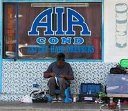 Five-foot-way Cobbler. A cobbler conducting his trade on the five-foot-way right in front of a barber shop royalty free stock photography
