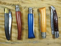 Five French folding pocket knives on a wooden surface stock photography