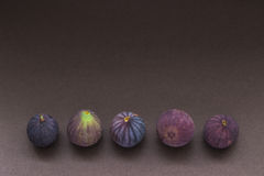 Five fresh figs in a row Royalty Free Stock Photos