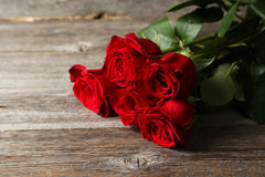 Five fresh red roses on wooden background Royalty Free Stock Photography