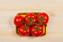 Five fresh red tomatoes with green stem in the tray , isolated on the background Royalty Free Stock Photography