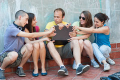 Five friends battling over a  laptop. Five friends having some disagreements what to use laptop for, battling each other to take it over Royalty Free Stock Photos