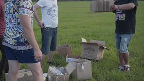 Five friends begin to collect homemade rocket from a pile of cardboard boxes in the field in the evening. Funniest moment stock footage