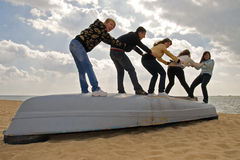 Five friends on the boat. Company of five friends having fun on the board of a boat standing on the sand Stock Photo