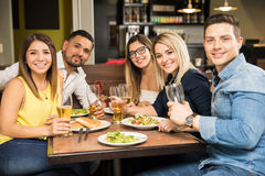 Five friends eating in a restaurant. Portrait of a group of five good looking Hispanic friends eating and drinking in a restaurant Royalty Free Stock Image