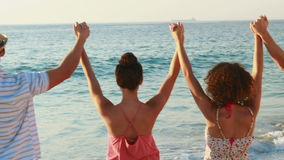 Five friends hand in hand standing at the beach