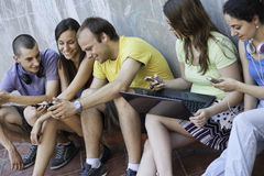Five friends having fun. A group of five young people having fun outdoors using modern multimedia technology Royalty Free Stock Image