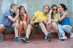 Five friends having fun. Five young people having fun together, whispering something to each other Stock Photo