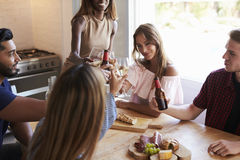 Five friends making a toast in the kitchen at a dinner party Stock Photography